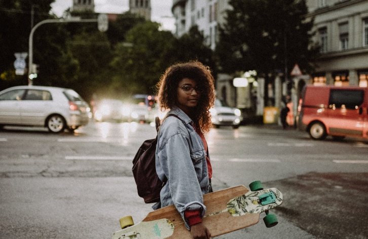 Person mit Skateboard in der Stadt © Photo by Kinga Cichewicz on Unsplash