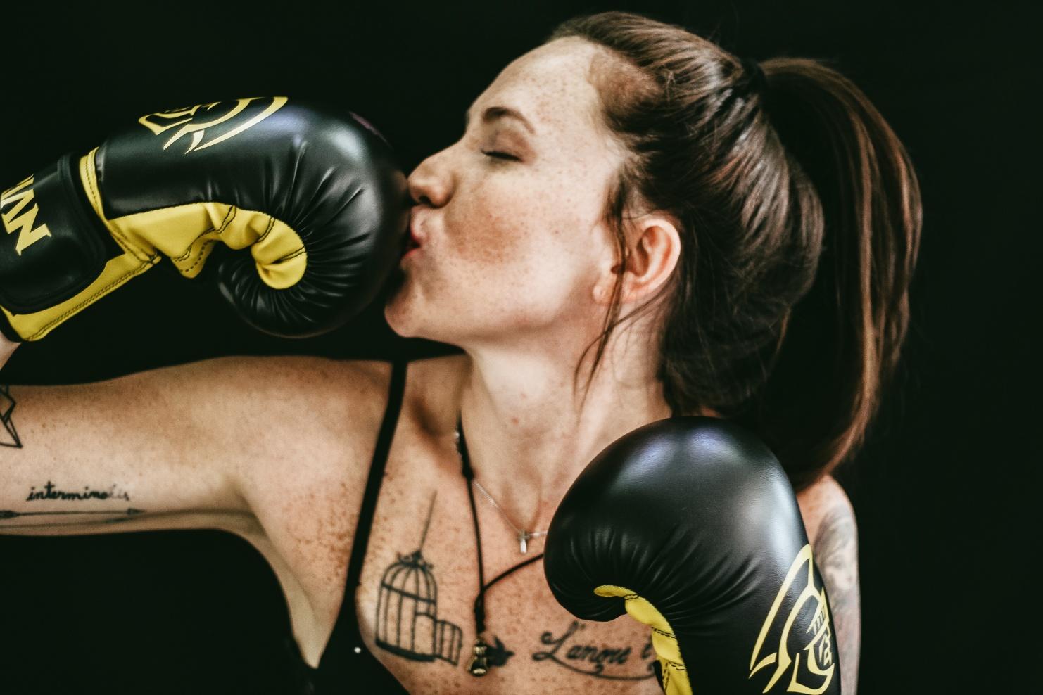 Boxerin küsst eine Hand im Boxhandschuh © Matheus Ferrero for Unsplash